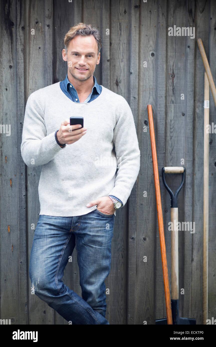 Porträt von reifer Mann mit Smartphone gegen Holzwand Stockbild