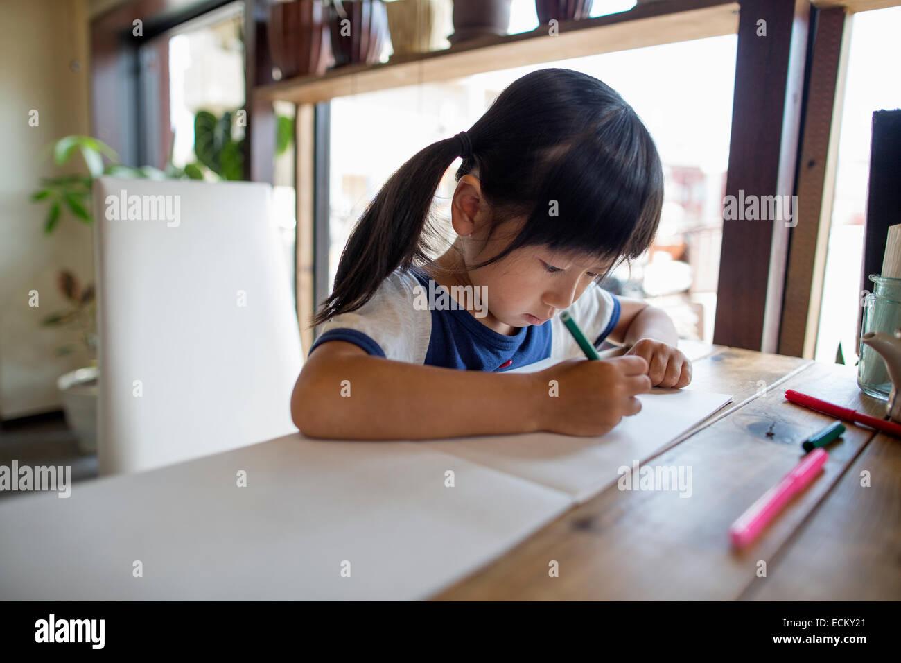 Mädchen mit Zöpfen sitzt an einem Tisch mit Filzstift Stifte Zeichnung. Stockbild
