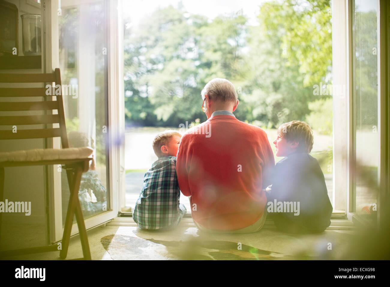 Großvater und Enkel sitzen in Tür Stockbild