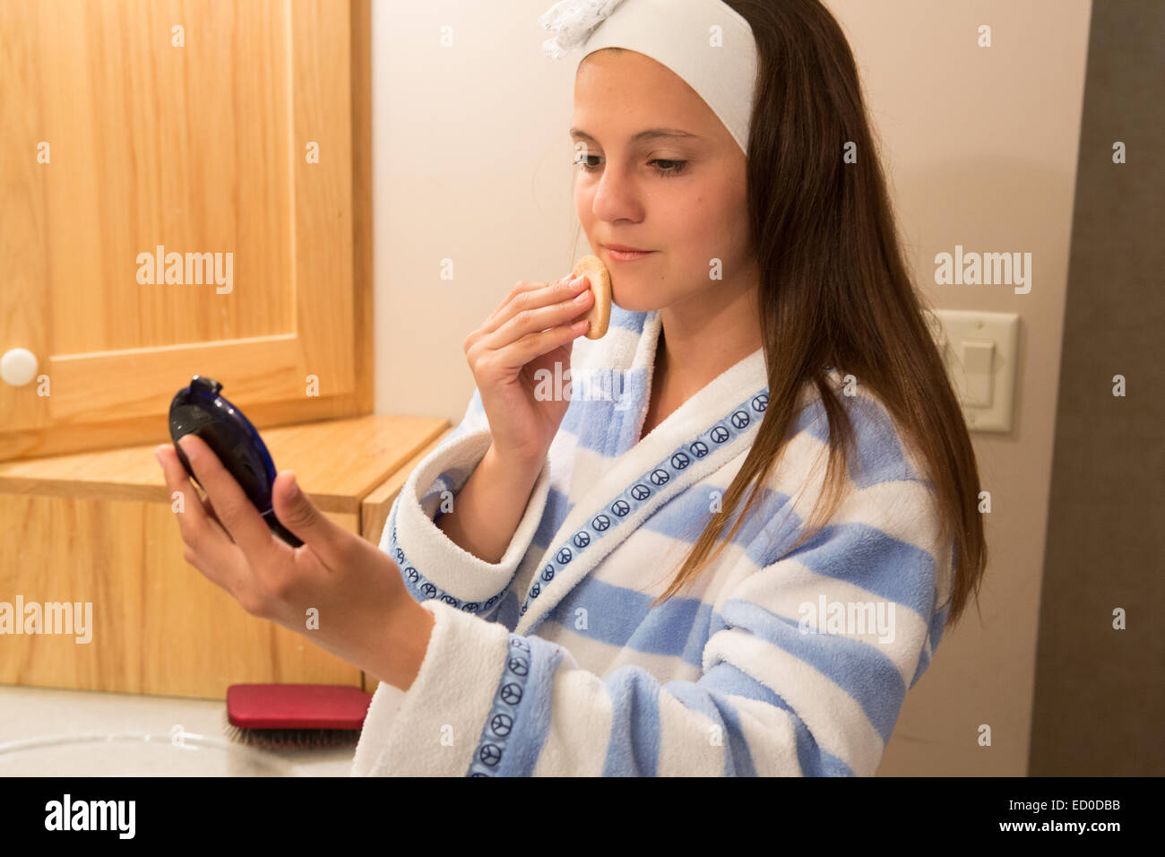 Mädchen stehen in Bad Auftragen von Puder foundation Stockbild