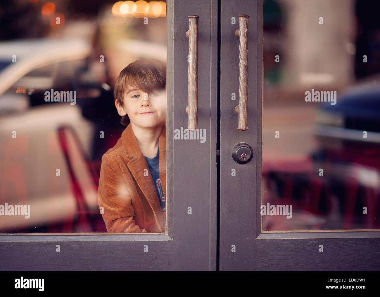 Junge auf der Suche durch Glastüren Stockbild