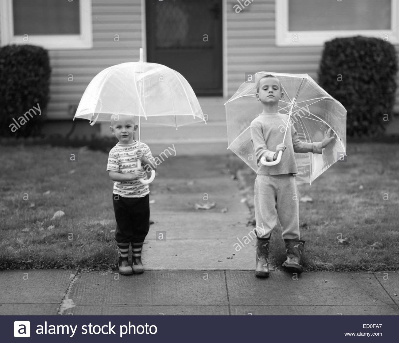 Brüder (2-3, 4-5) mit Sonnenschirmen, Portland, Oregon, USA Stockbild