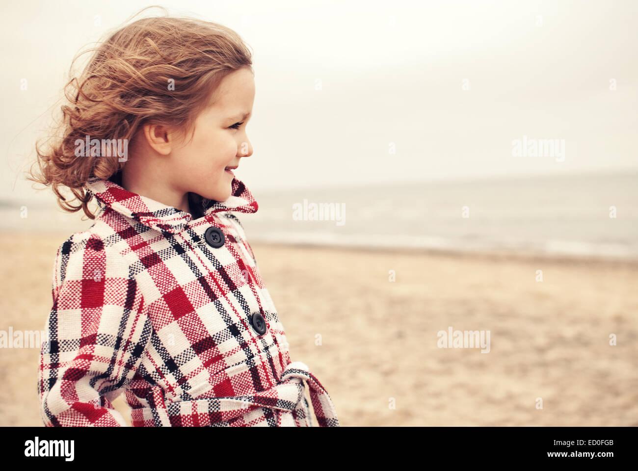 Kleines Mädchen (2-3) in Mantel am Strand Stockbild