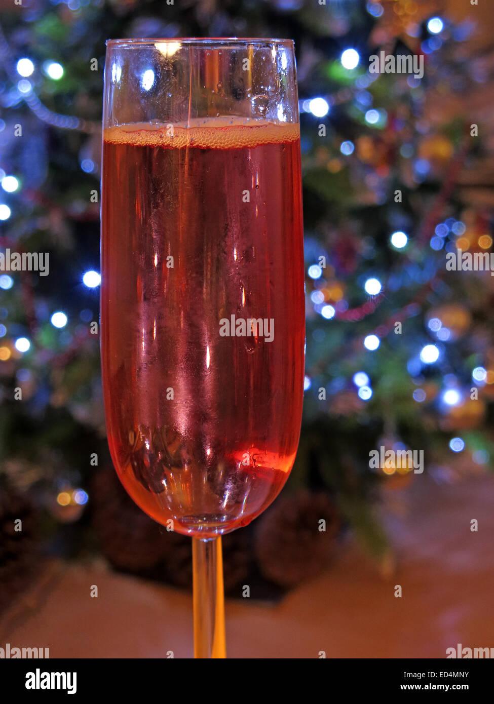 Laden Sie dieses Alamy Stockfoto Gefahren des festlichen Trinkglas, ein mehr von Roséwein zu Weihnachten, vor Baum von Dekorationen - volles Glas fizz - ED4MNY
