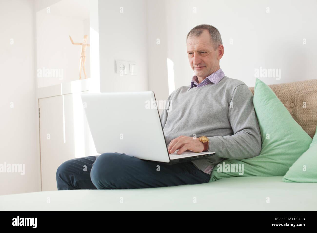 Erwachsener Mann mit einem Laptop zu Hause Stockbild