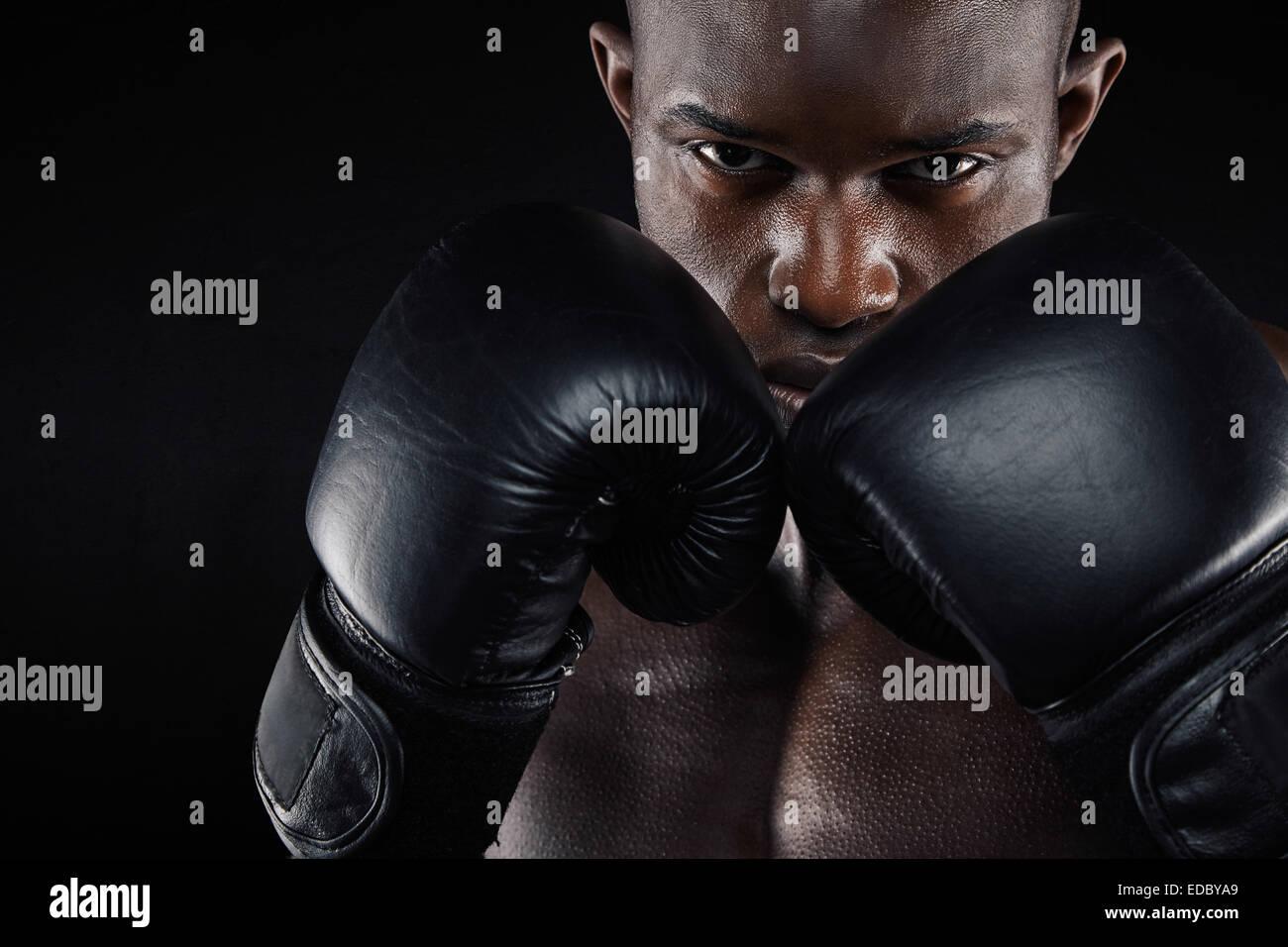 Porträt eines jungen männlichen Boxer in Kampfposition auf schwarzem Hintergrund. Junger Mann Sport Boxen. Stockbild