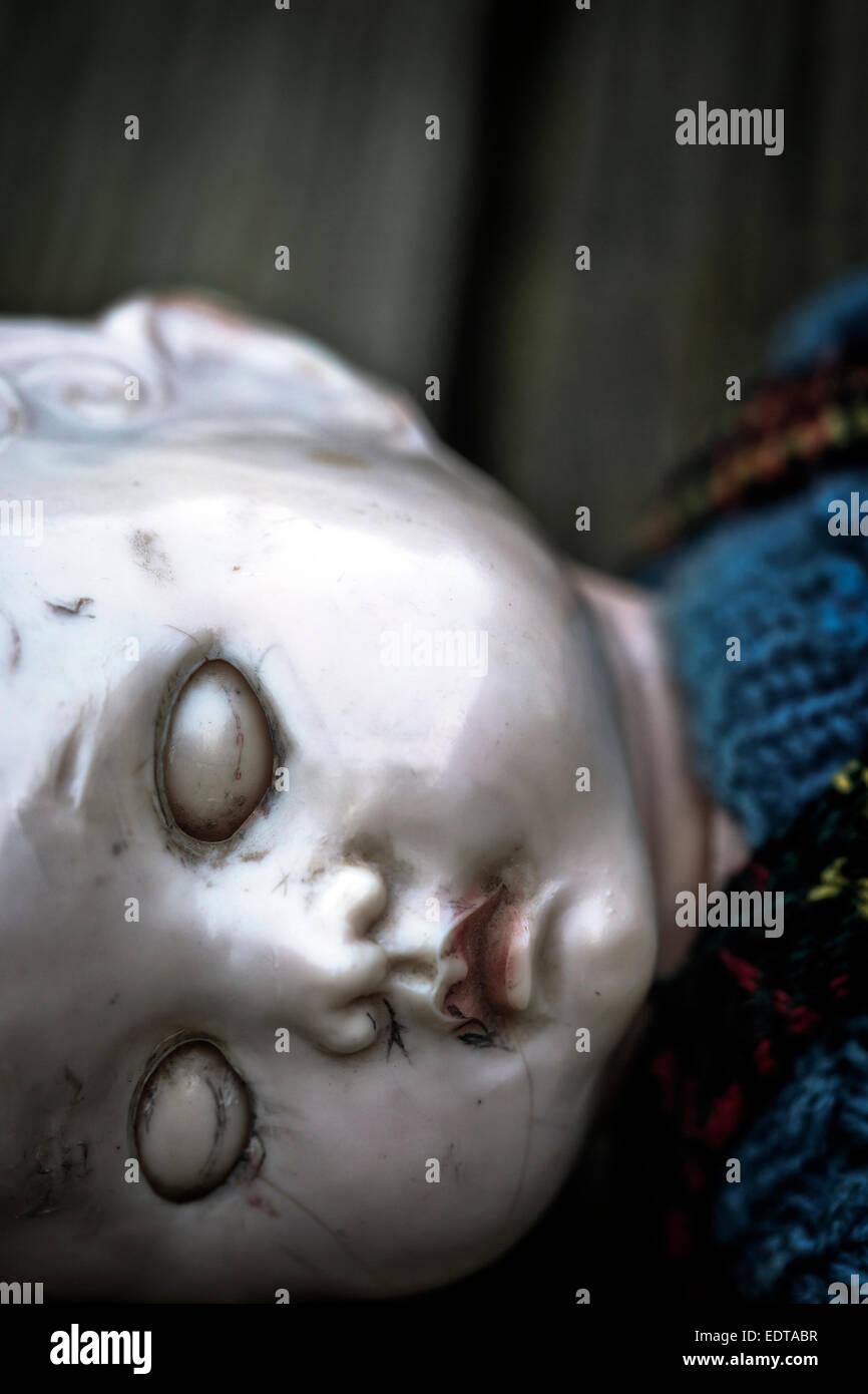 eine alte und zerbrochene Puppe mit geschlossenen Augen Stockbild