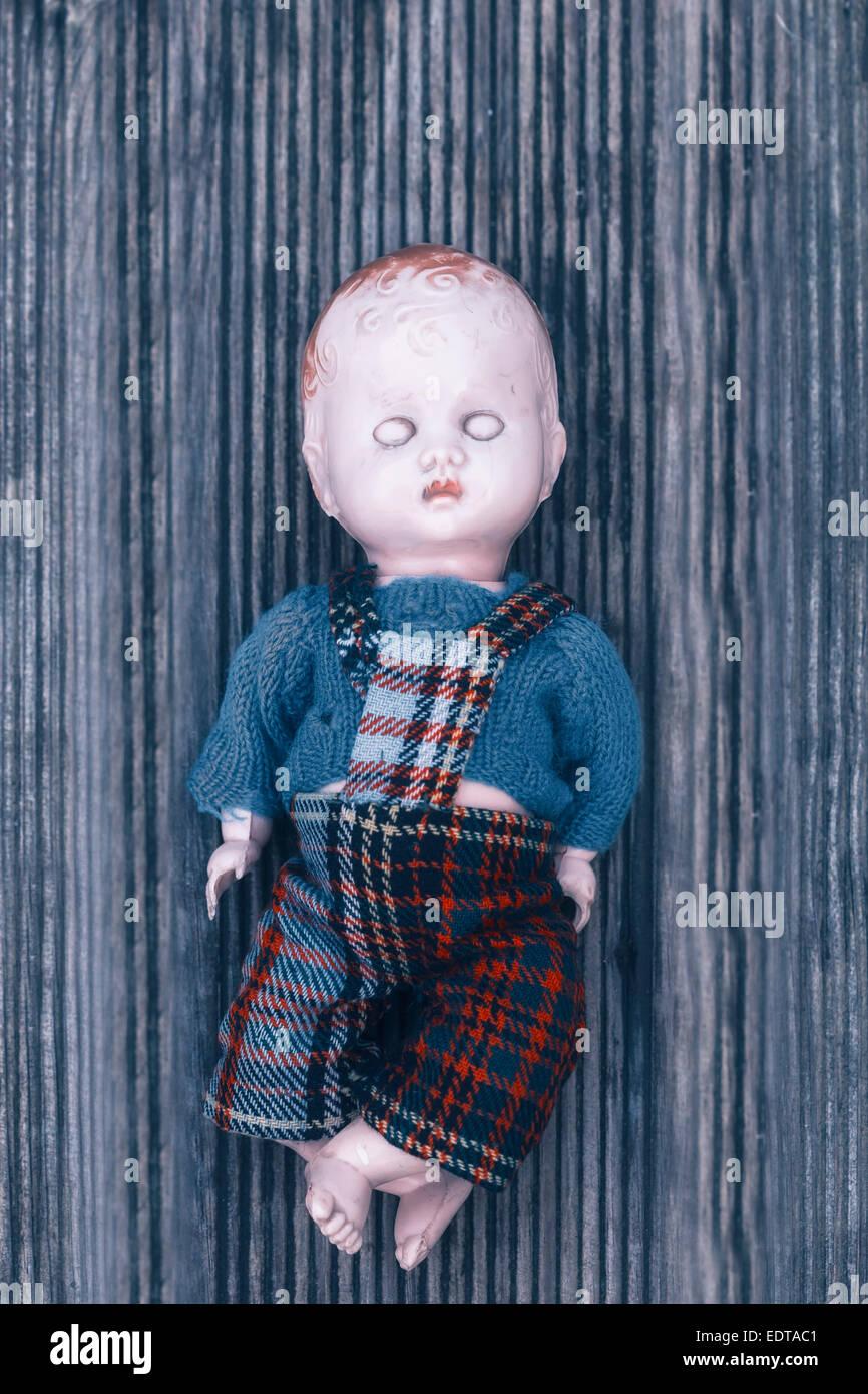 eine kaputte Puppe auf einem Holzfußboden Stockbild