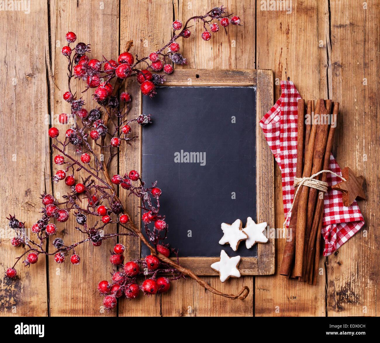 Vintage Weihnachten Hintergrund mit Kreide an Bord, Zweig mit roten Beeren, Weihnachten Plätzchen und Zimtstangen Stockbild