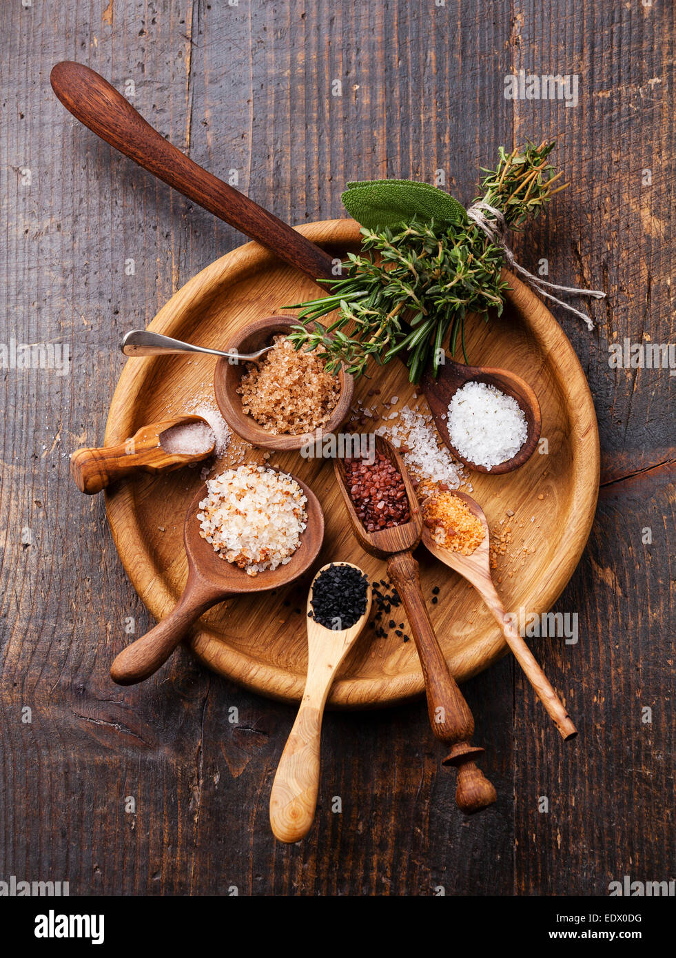 Verschiedene Arten von Lebensmitteln grobes Salz in Holzlöffel auf dunklem Hintergrund Stockbild