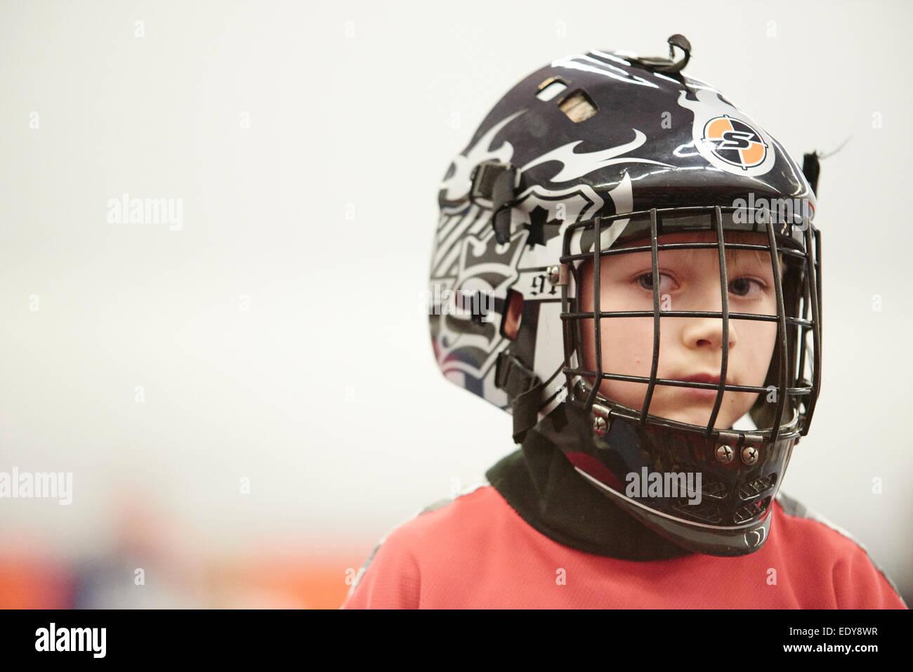Kinder jungen Schüler spielen Floorball (Unihockey) entsprechen in Schule Turnhalle mit Kunststoff Hockeyschläger Stockbild