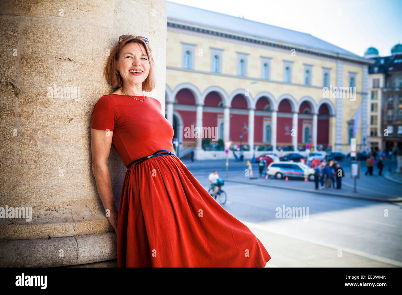 Ältere Frau lehnt sich an Säule lächelt glücklich, München, Bayern, Deutschland Stockbild