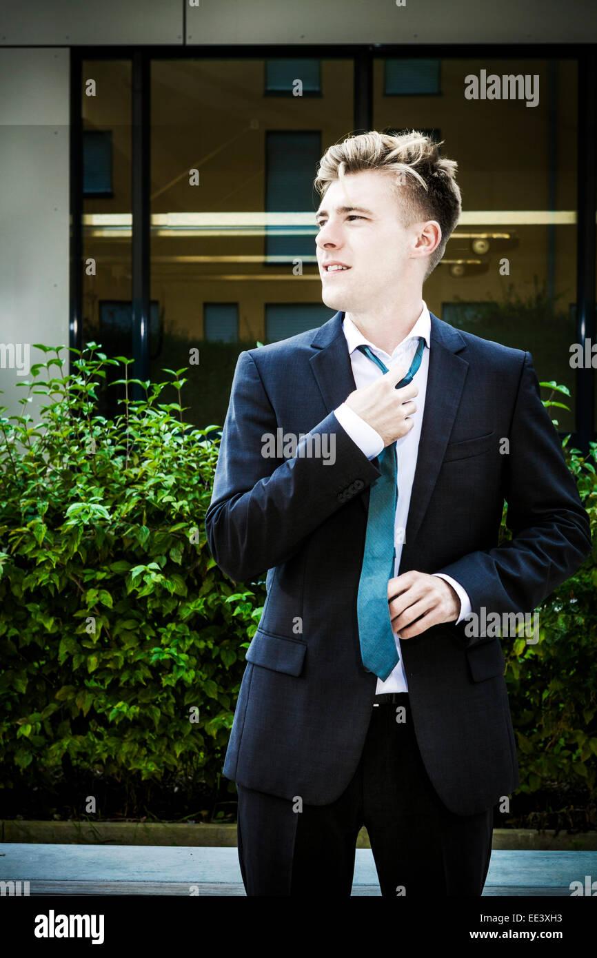 Junger Geschäftsmann Anpassung seine Krawatte, München, Bayern, Deutschland Stockbild