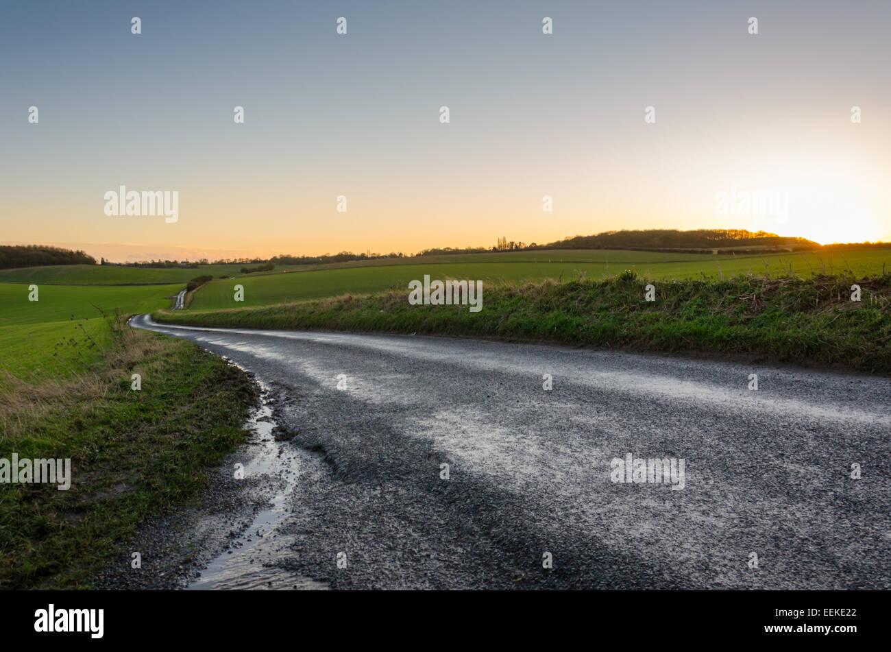 Sonnenuntergang über einem nassen Landstraße im Vereinigten Königreich Stockbild