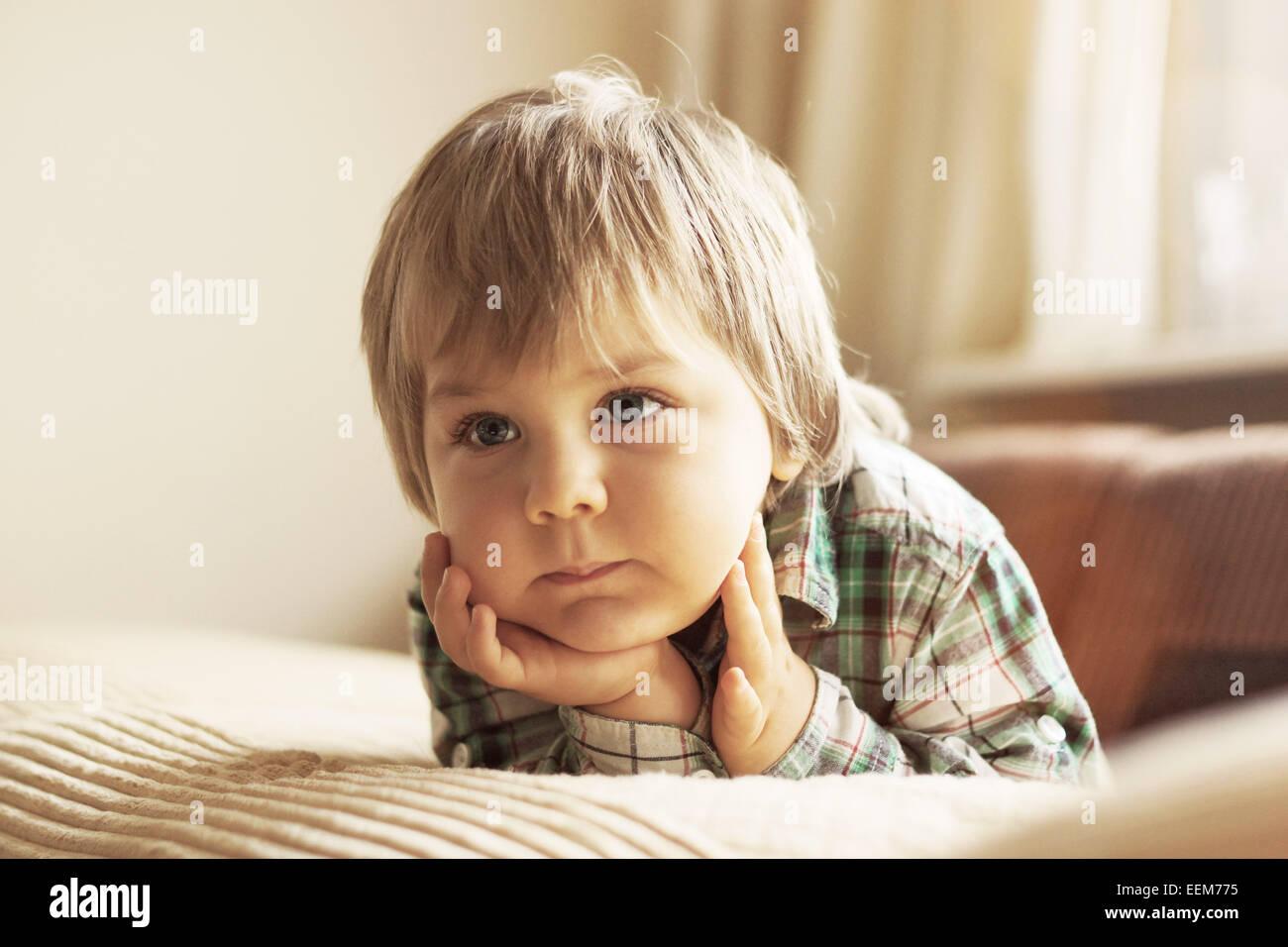 Porträt eines jungen auf Bett liegend Stockbild