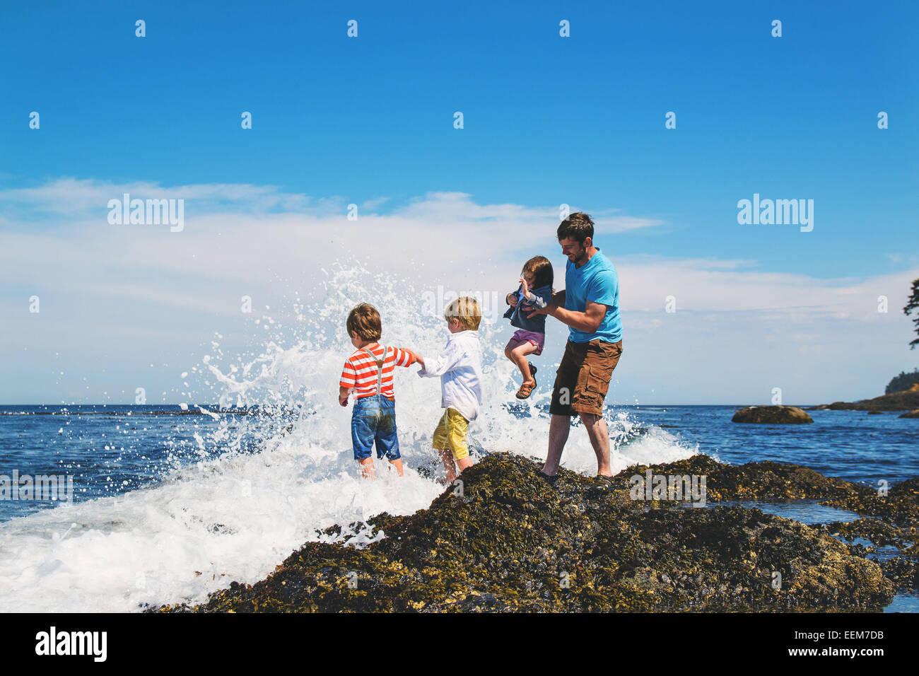 Vater und drei Kinder (2-3, 4-5) spielen in Wellen Stockbild