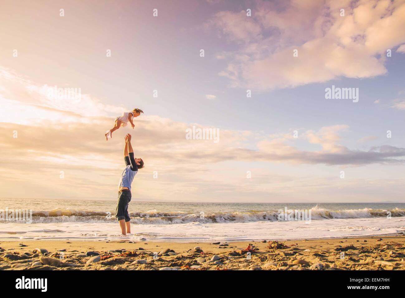 Vater warf junges Mädchen (2-3) in Luft am Strand Stockbild