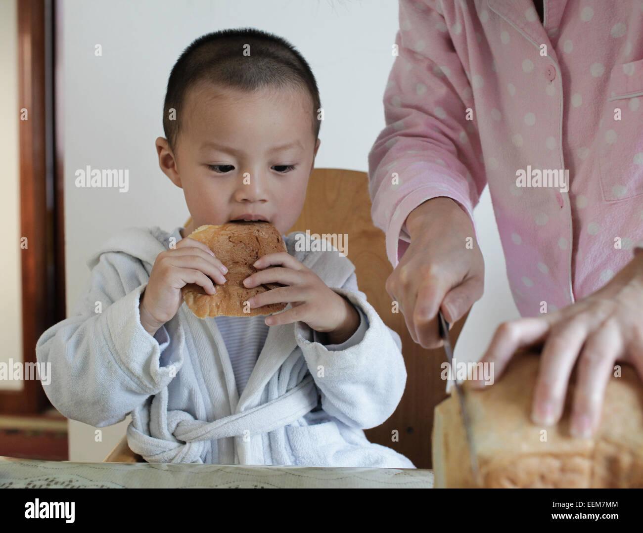 Jungen (2-3) beim Frühstück Stockbild