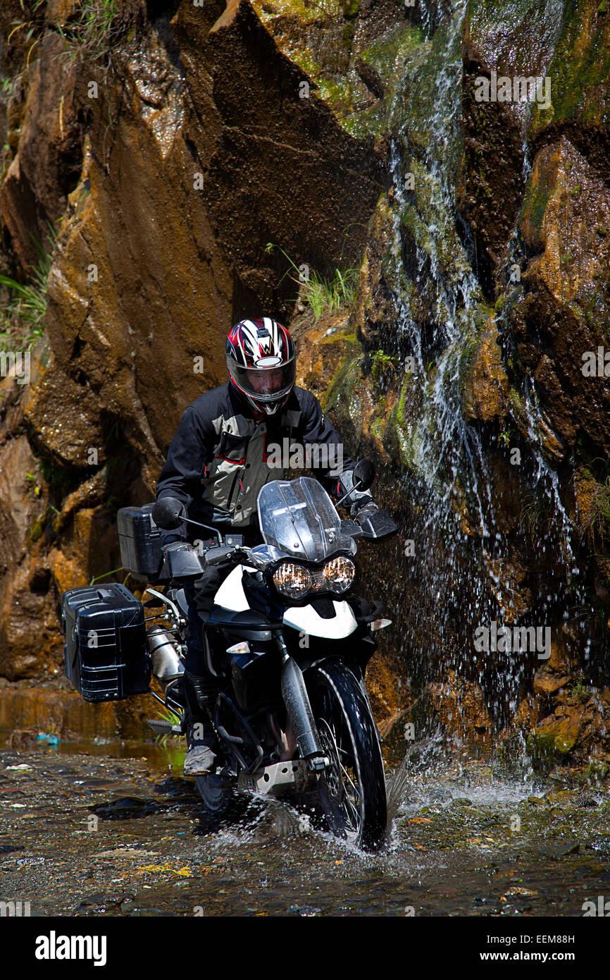 Ecuador, Mann auf Motorradfahren unter Wasserfall Stockbild