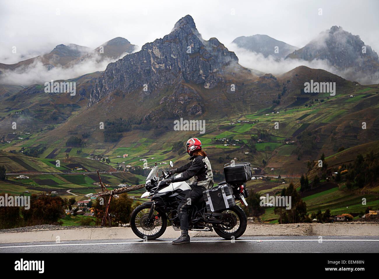 Ecuador, Mann auf Fahrrad am Straßenrand mit Bergkette im Hintergrund Stockbild