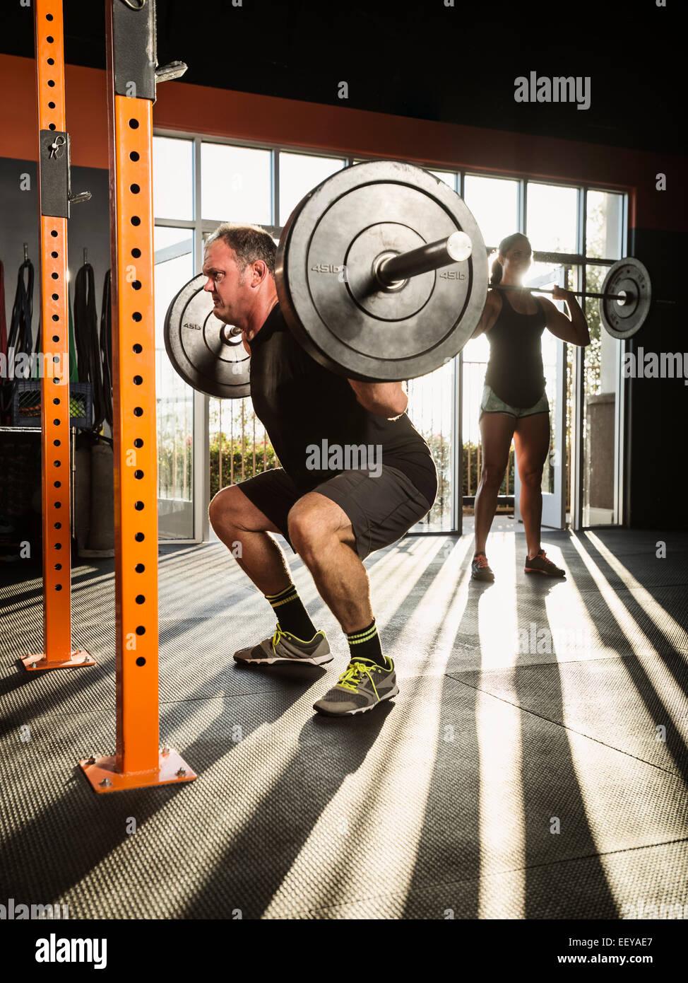 Mann und Frau im Fitness-Studio trainieren Stockbild