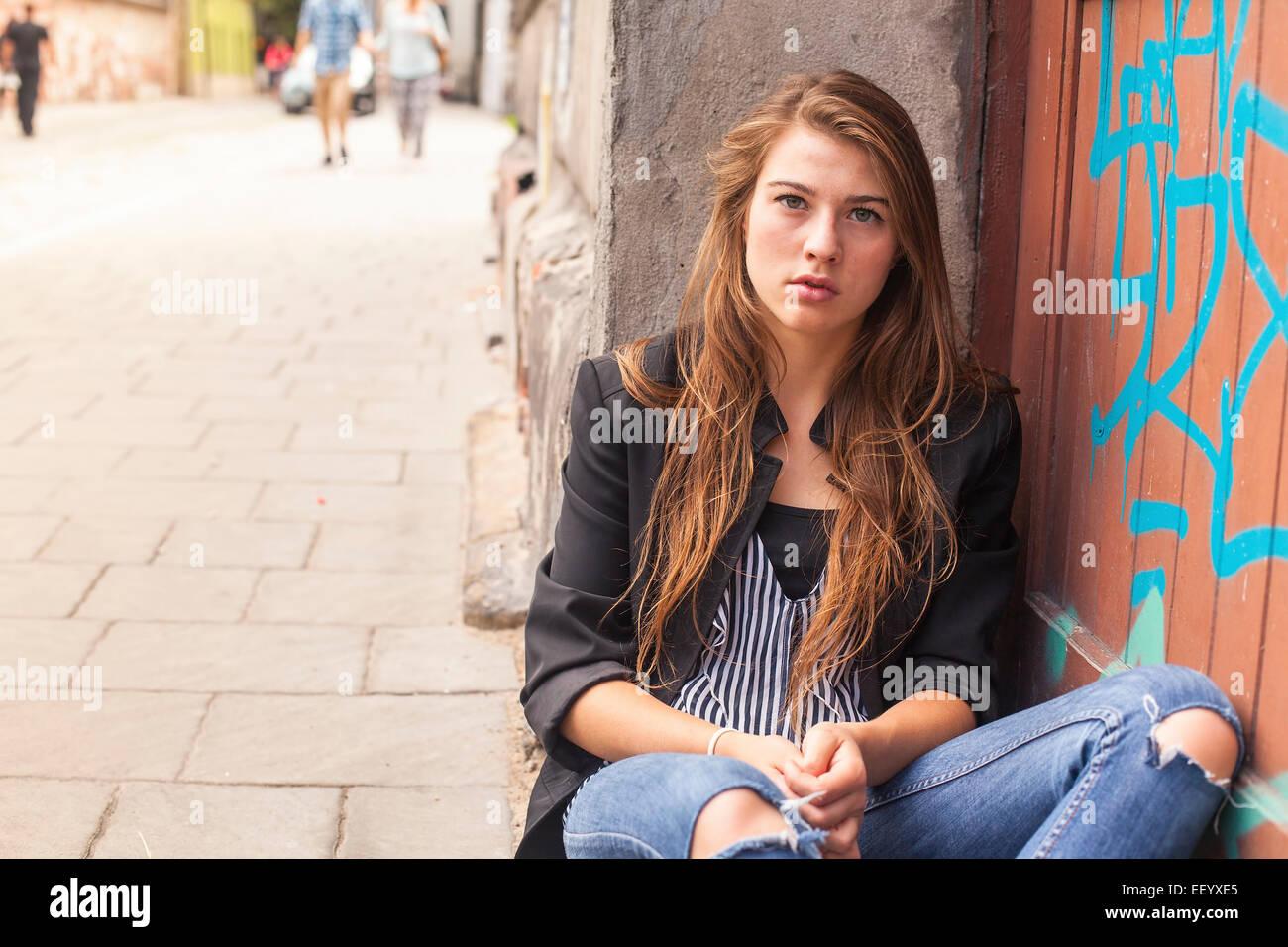 Junge Hipster Mädchen sitzen auf der Straße. Stockfoto