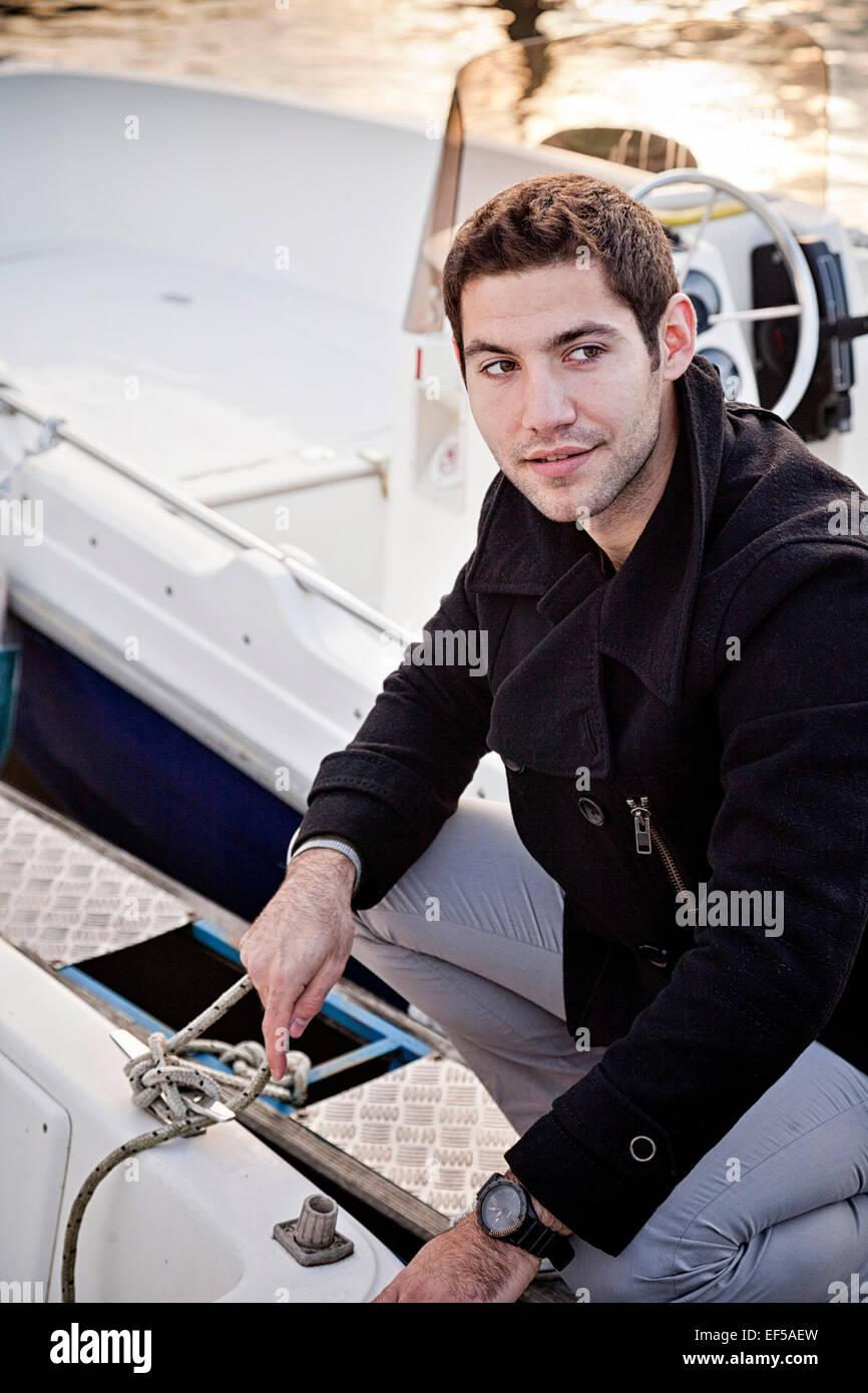 Junger Mann binden Seil Motorboot Stockbild