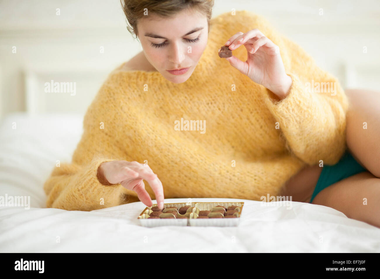 Frau auf Bett Schokolade essen Stockbild
