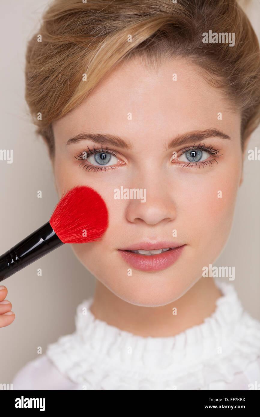 Porträt einer Frau mit Make-up Pinsel auf ihr Gesicht Stockbild