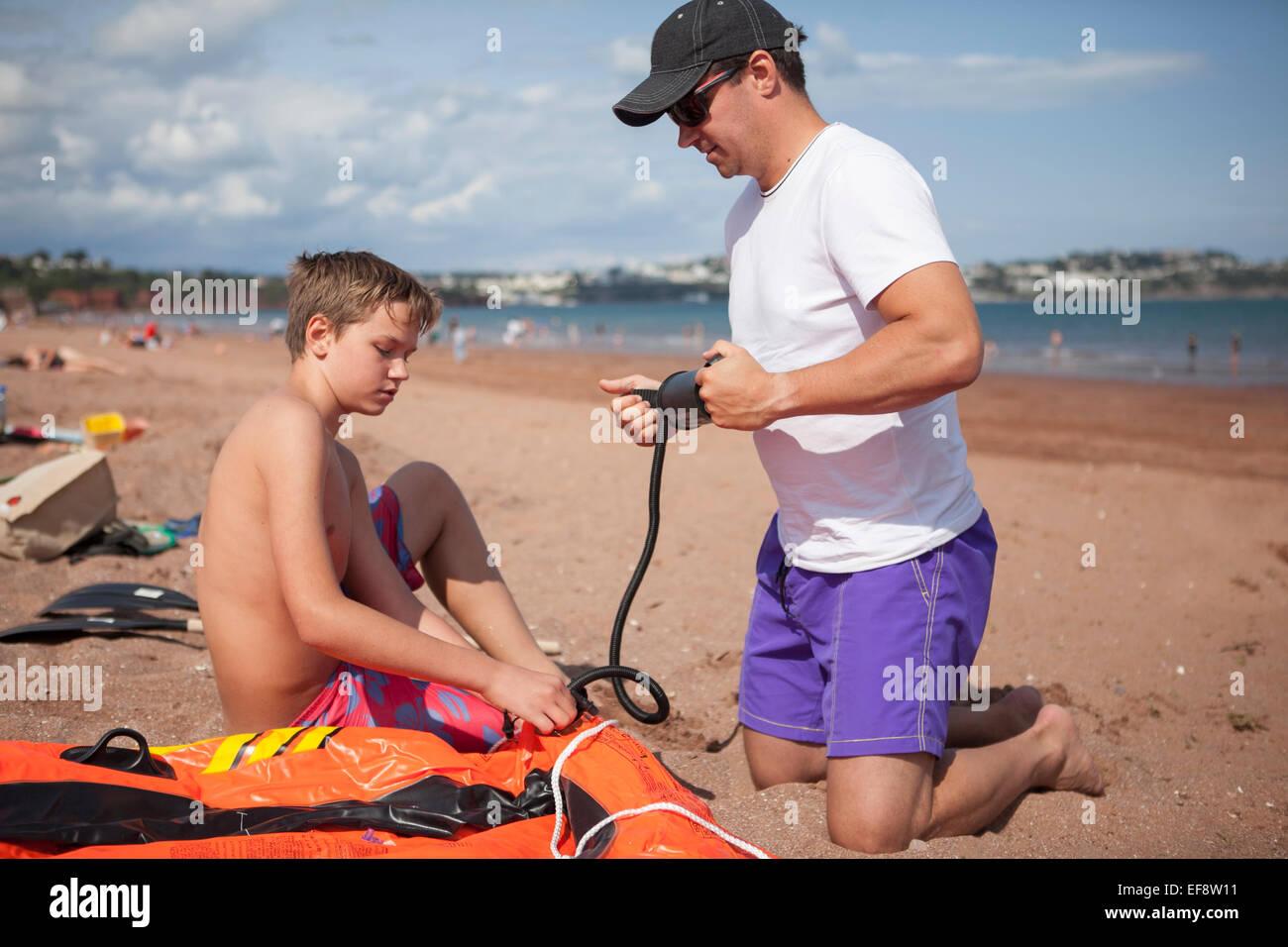 Vater und Sohn (12-13) aufblasen Boot am Strand Stockbild