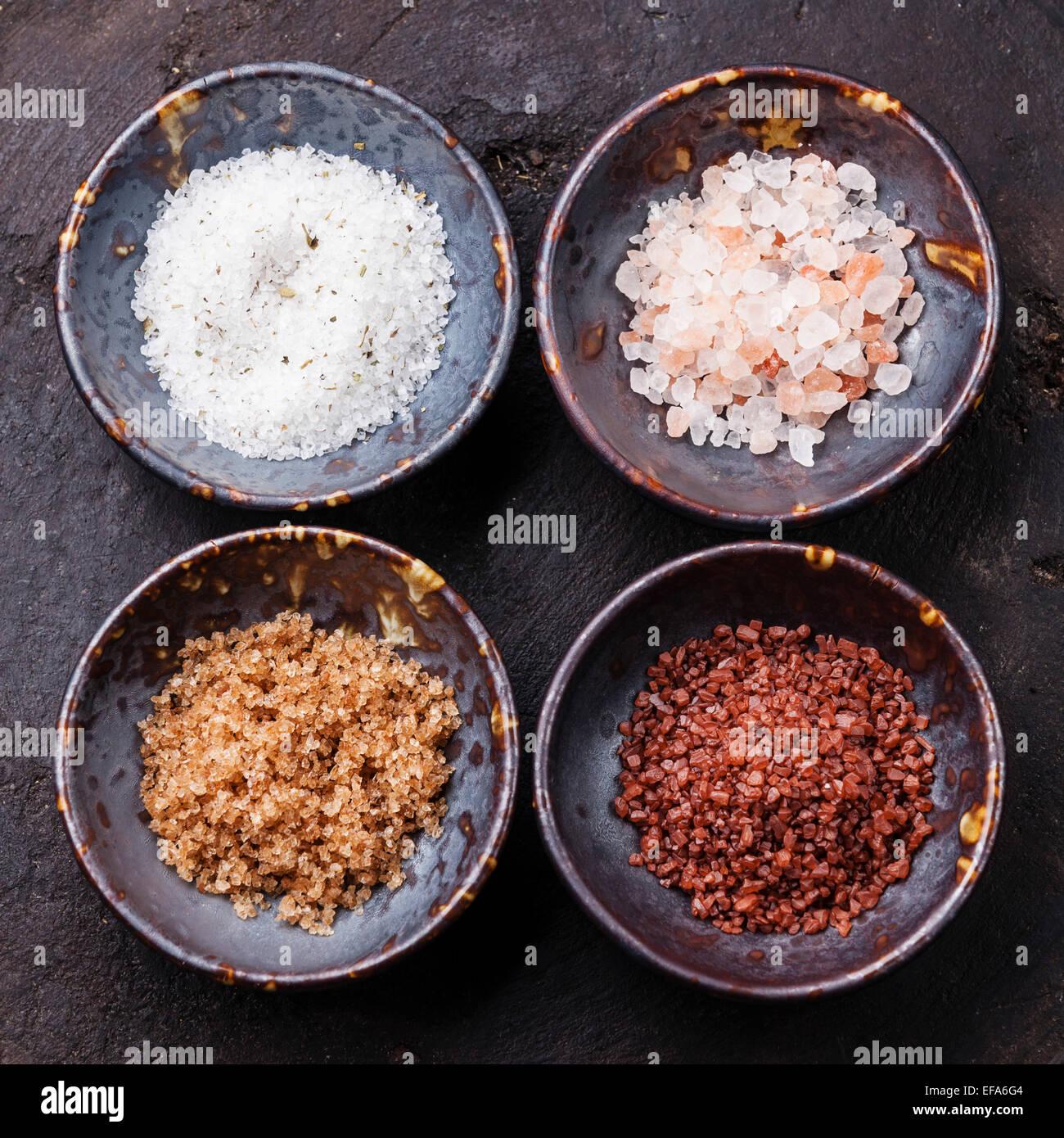 Verschiedene Arten von Lebensmitteln grobes Salz in Keramikschalen auf dunklem Hintergrund Stockbild
