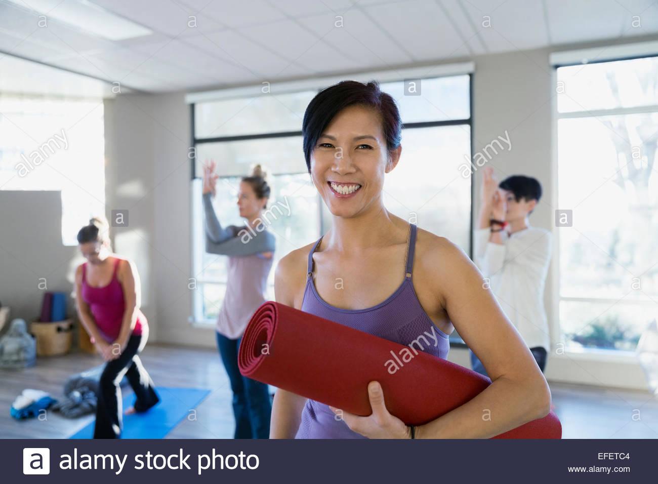 Portrait von lächelnden Frau mit Yoga-Matte Stockbild
