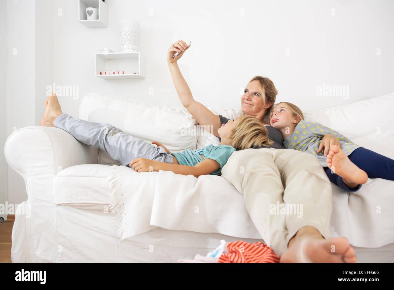Mutter, Tochter und Sohn auf Couch nehmen ein Selbstporträt Stockfoto