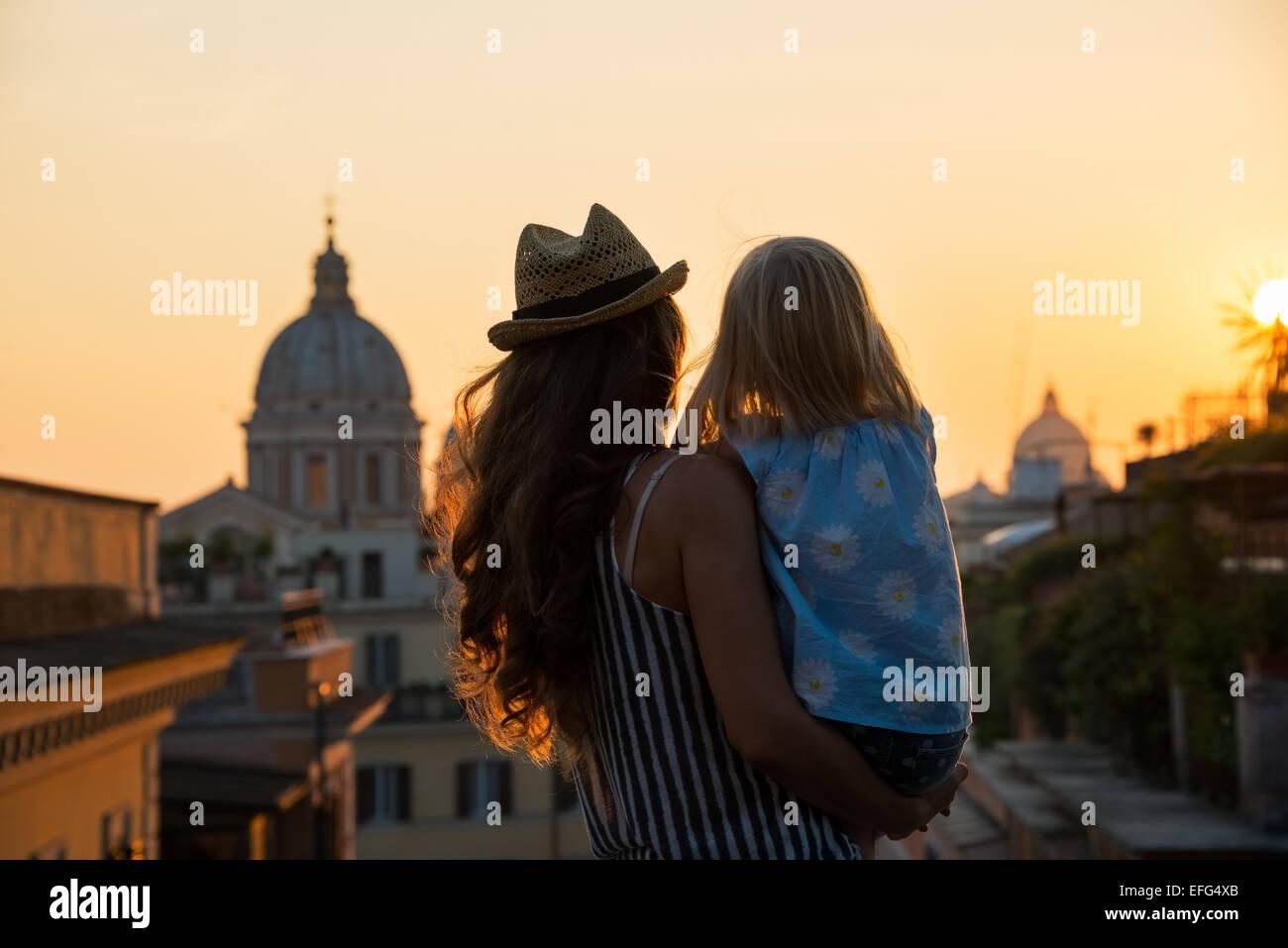 Silhouette von Mutter und Baby Mädchen auf der Suche auf den Dächern von Rom am Sonnenuntergang. Rückansicht Stockbild