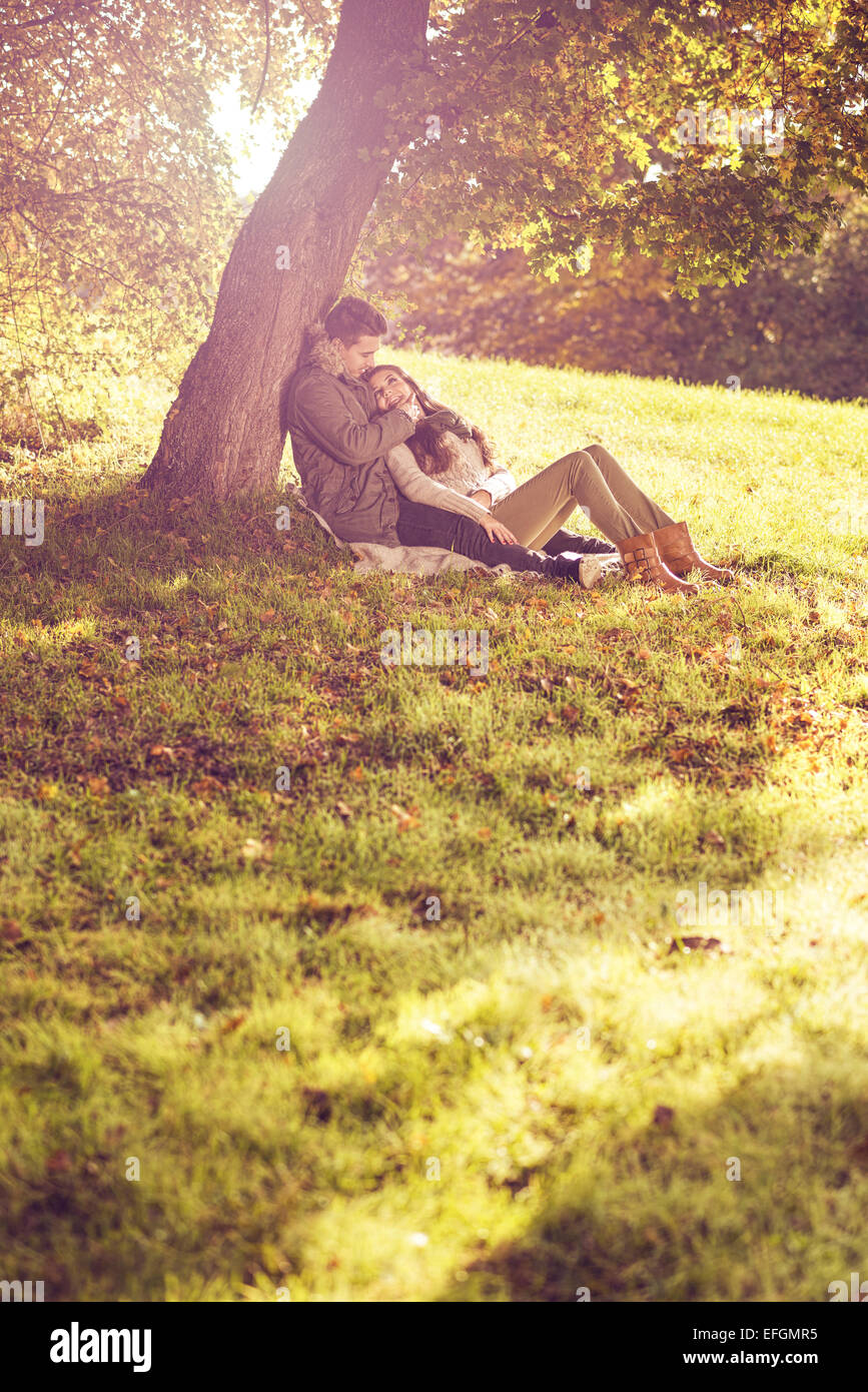 Liebespaar sitzt unter einem Baum in den bunten Herbstwald Stockbild