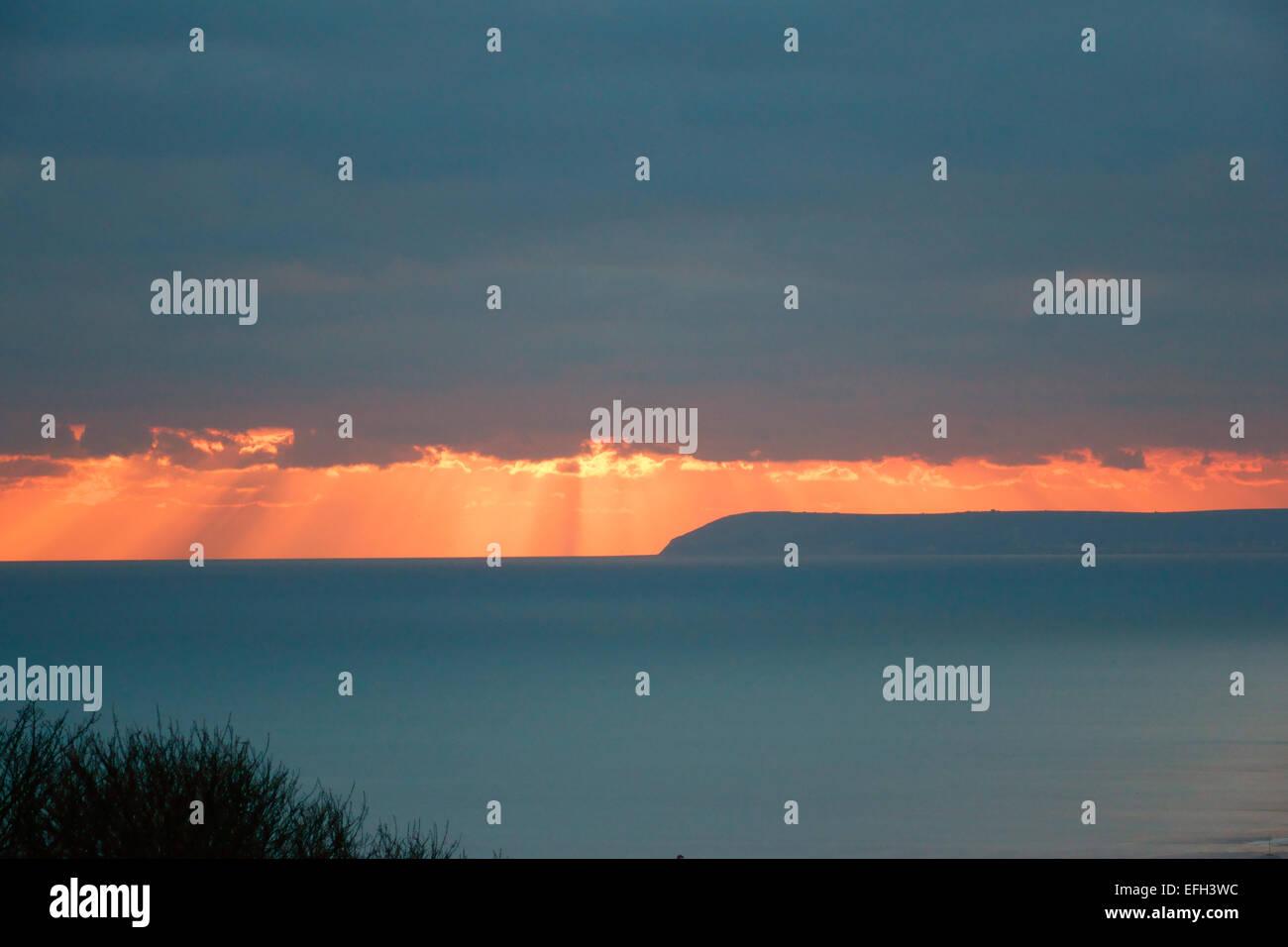 Hastings, East Sussex, England, UK. Die dramatische winter Sonnenuntergang Blick von Hastings wie die Sonne über Stockbild