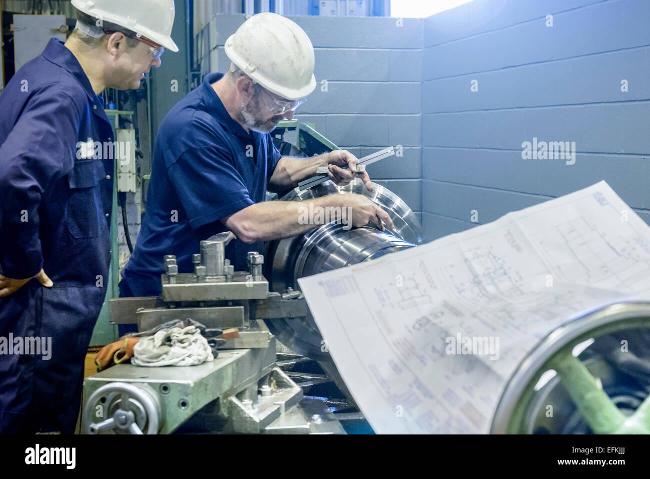 Ingenieure arbeiten an Drehbank mit Zeichnungen Stockbild