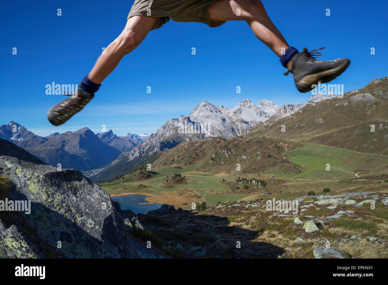 Beine des männlichen Wanderer springen über Felsen, Lai da Fons, Kanton Graubünden, Schweiz Stockbild