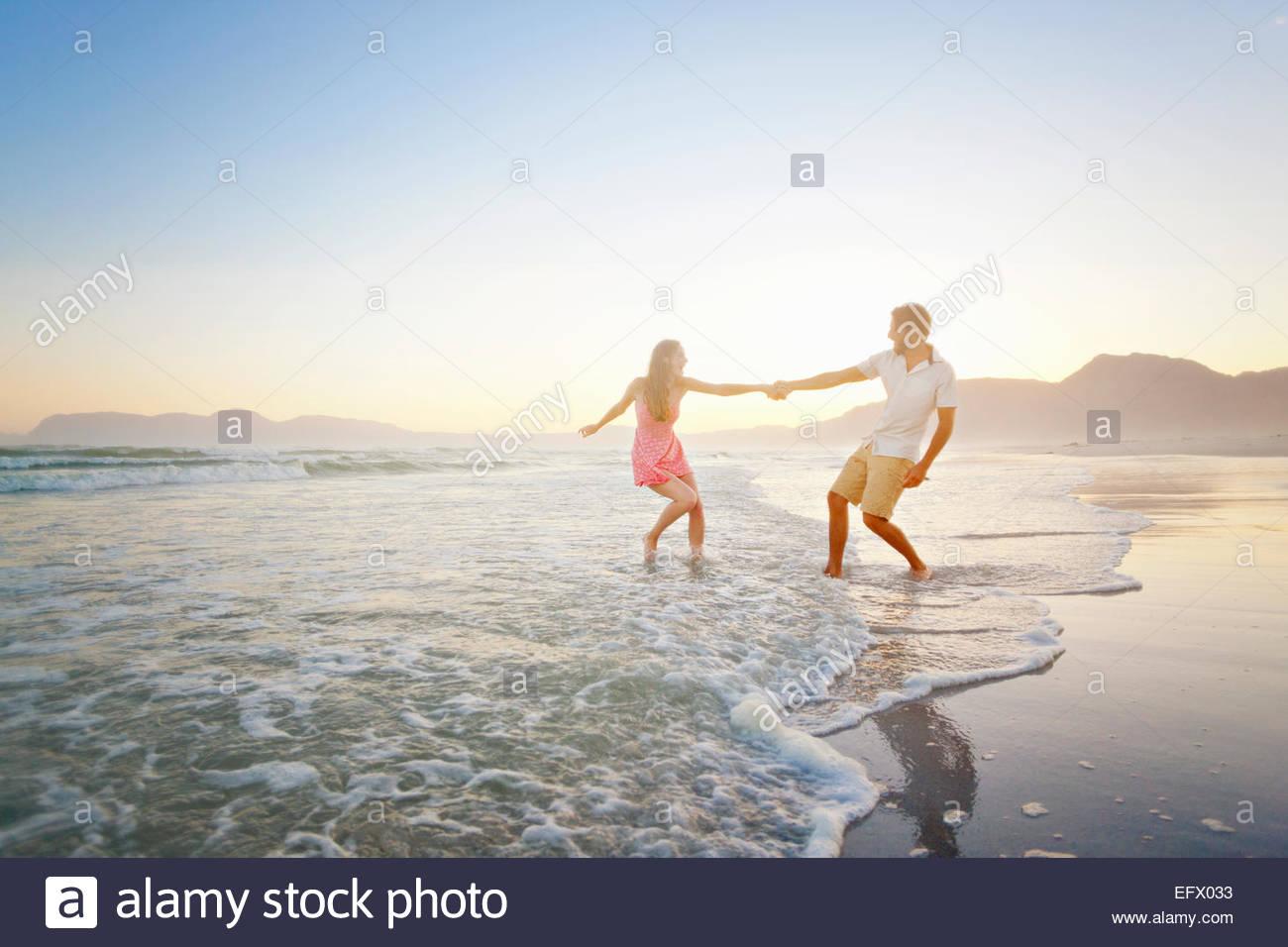 Paar, Hand in Hand, spielerisch zu Fuß durch Wellen am Sonnenstrand Stockbild