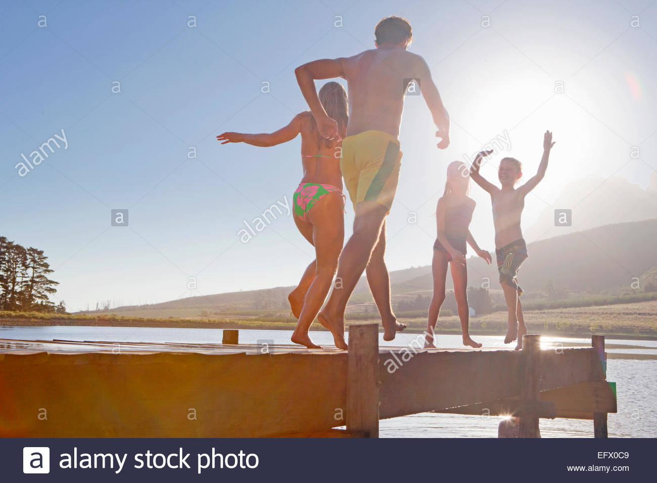 Glückliche Familie laufen und springen auf Steg Stockbild