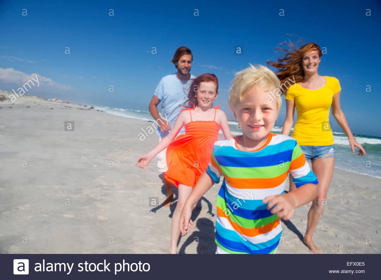 Glückliche Familie läuft in Richtung Kamera, am sonnigen Strand Stockbild