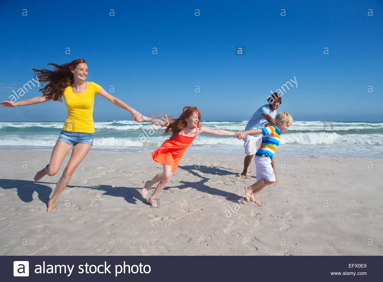 Glückliche Familie Hand in Hand, laufen und ziehen einander entlang Sonnenstrand Stockbild