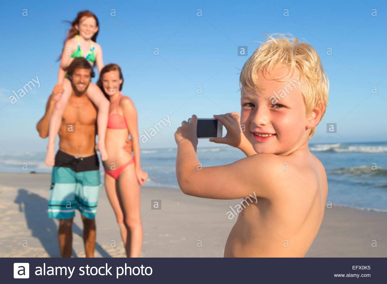 Junge, lächelnd in die Kamera, Aufnahme der Familie am Sonnenstrand Stockbild