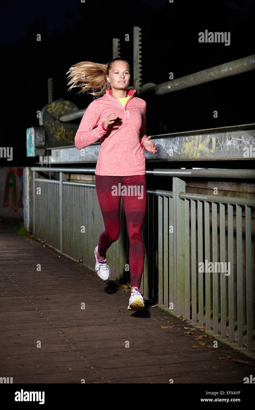 Junge Frau läuft am Steg in der Nacht Stockbild