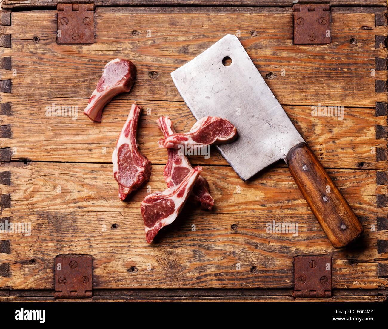 Rohes, frisches Lamm Rippen und Fleischerbeil auf hölzernen Hintergrund Stockbild