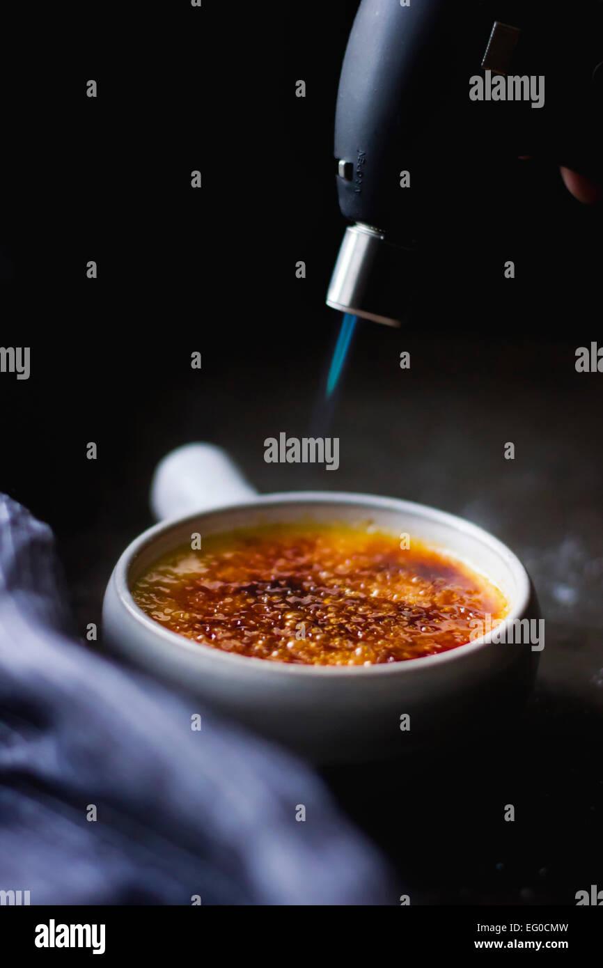 Schmelzende Zucker auf eine Crème brûlée Dessert mit einer Lötlampe Stockbild