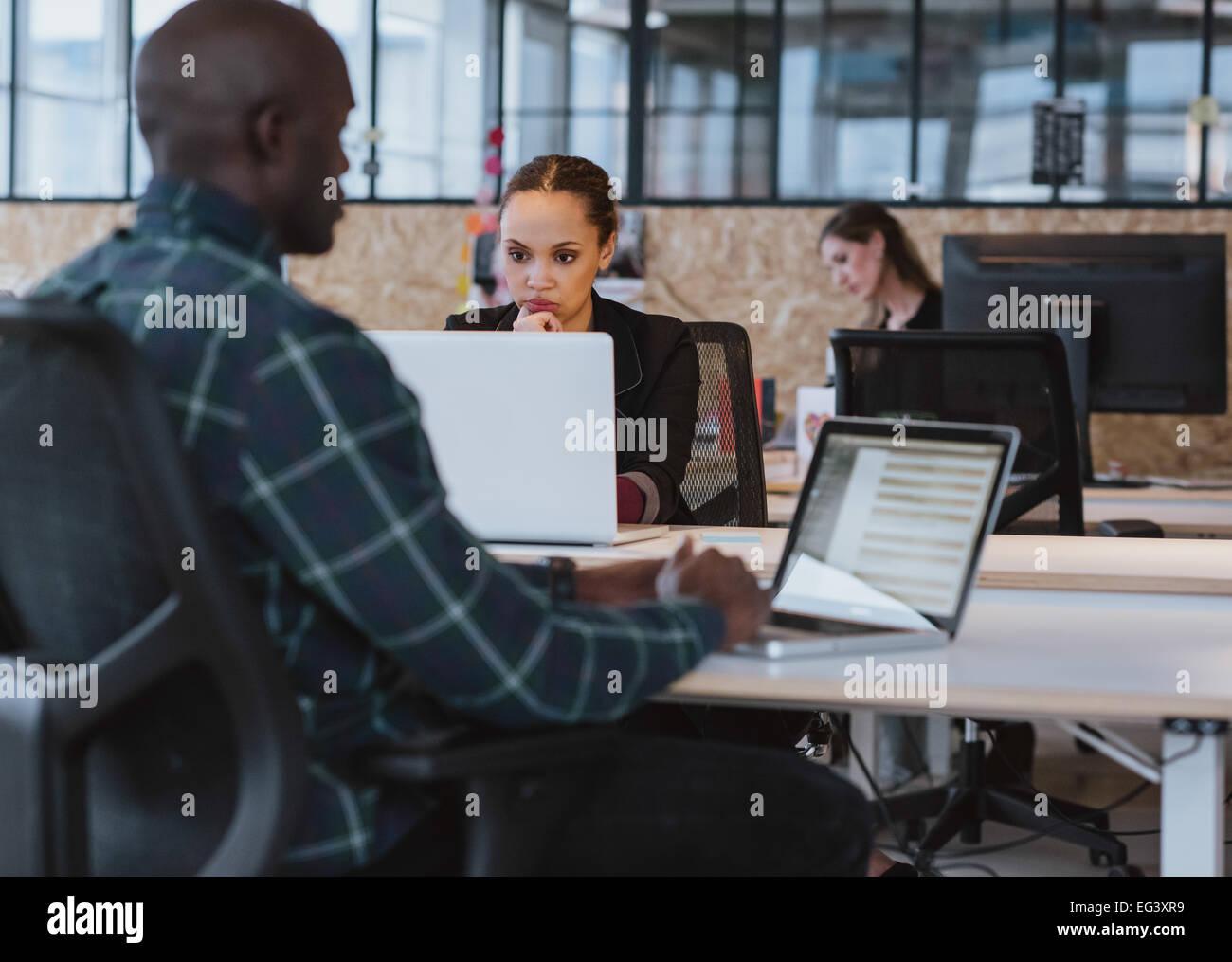 Junge afrikanische Frau sitzt an ihrem Schreibtisch arbeiten auf Laptop-Computer. Geschäftsfrau Laptop-Bildschirm Stockbild