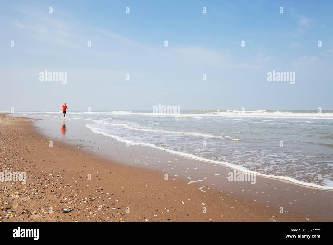 Belgien, Flandern, Mann Joggen am Meer Stockbild