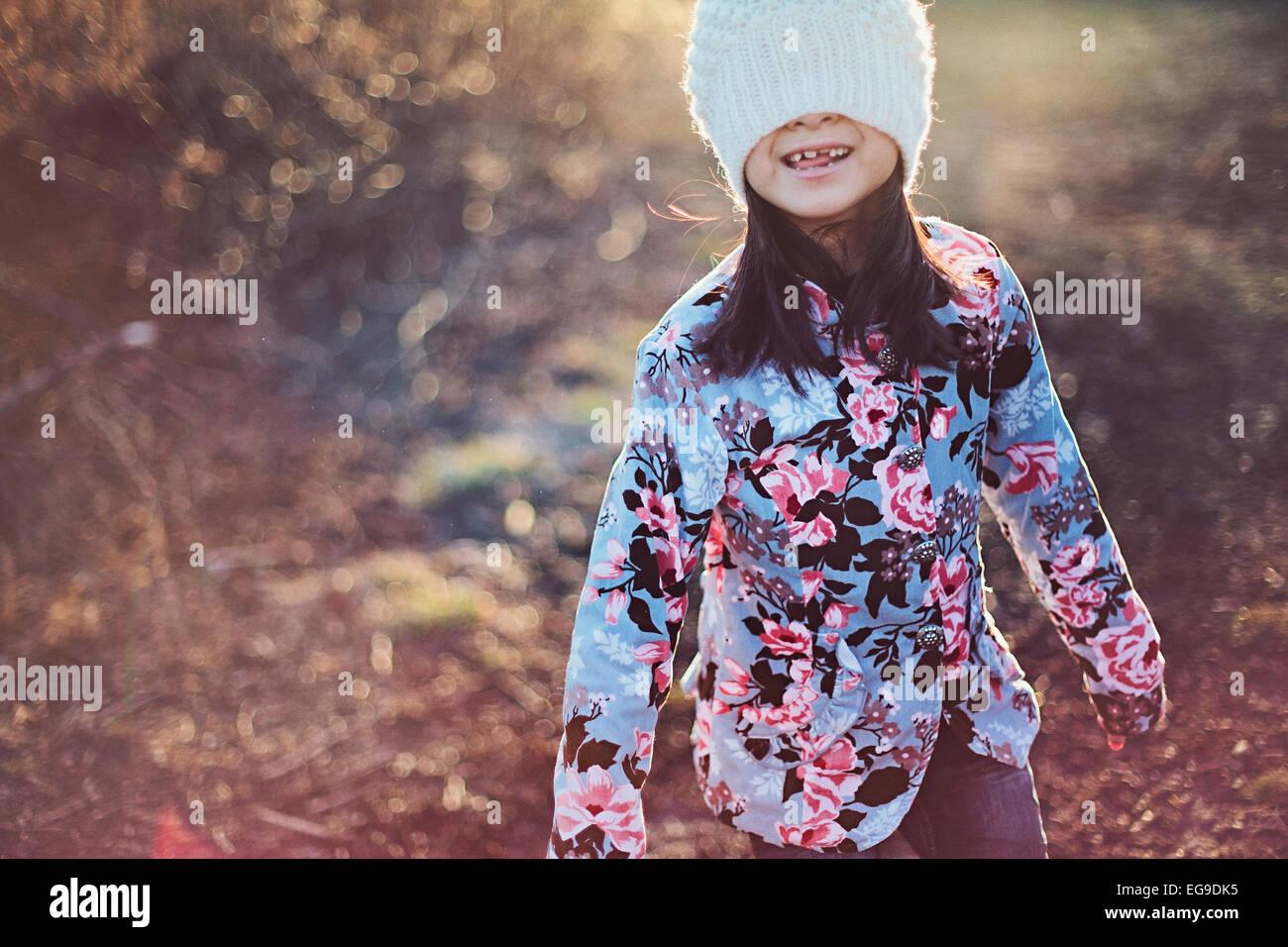 Mädchen (8-9) Verkleidung Gesicht mit weißen Wintermütze Stockbild