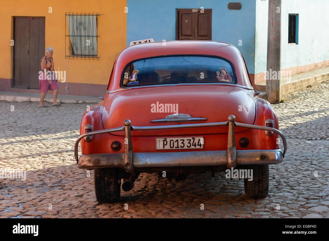 Eine rote kubanische Oldtimer Fahrt entlang einer gepflasterten Straße in Trinidad, Kuba Stockbild